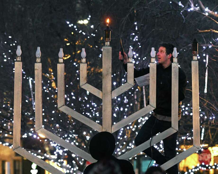 New President of Stamford's Downtown Special Services District David Kooris lights a candle on a giant menorah at Chabad of Stamford's Experience Chanukah at Latham Park in Stamford, Conn. Sunday, Dec. 22, 2019. Folks celebrated the first night of Chanukah with a giant outdoor menorah lighting, as well as gelt drop, olive oil press demostration, live music and latkes. Photo: Tyler Sizemore / Hearst Connecticut Media / Greenwich Time