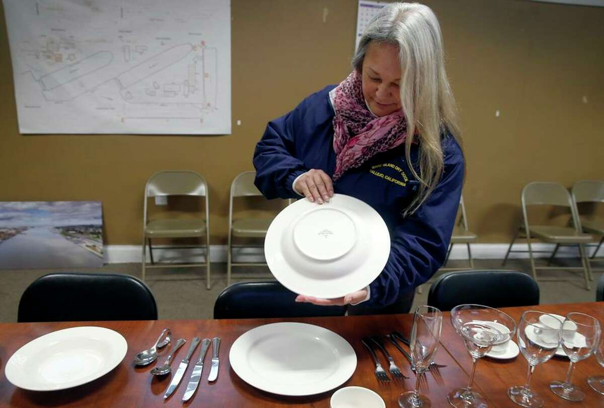 Christina Snyder, executive vice president of Mare Island Dry Dock, holds dishware that was salvaged from the Sherman.