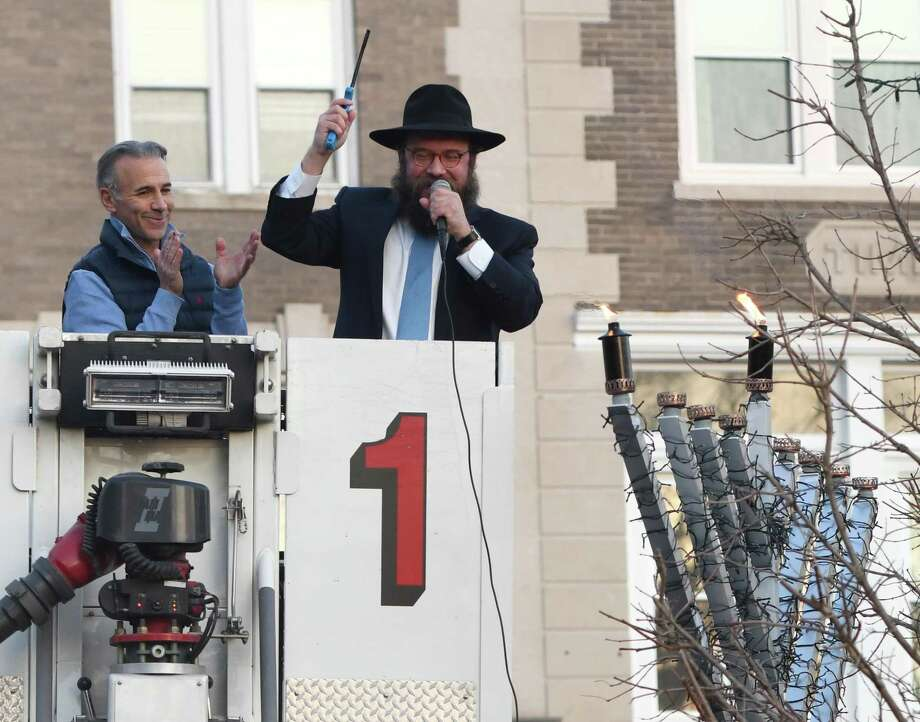 Rabbi Yossi Deren, right, celebrates with First Selectman Fred Camillo from atop Truck 1 from the Greenwich Fire Department after lighting a candle for the first night of Chanukah at Chabad of Greenwich's Chanukah Wonderland on Sunday. The first night of Chanukah with a giant outdoor menorah lighting, as well as donut decorating, arts and crafts, music, a virtural reality tour, and the Chanukah story as told by Judah Maccabee. Photo: Tyler Sizemore / Hearst Connecticut Media / Greenwich Time