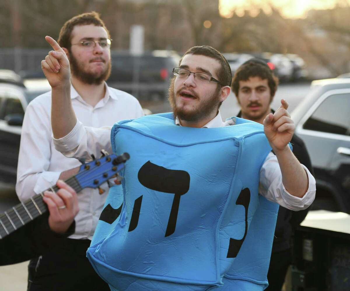 Berel Marozov dances while dressed as a dreidel at Chabad of Greenwich's Chanukah Wonderland on Greenwich Avenue in Greenwich, Conn. Sunday, Dec. 22, 2019. Folks celebrated the first night of Chanukah with a giant outdoor menorah lighting, as well as donut decorating, arts and crafts, music, a virtural reality tour, and the Chanukah story as told by Judah Maccabee.