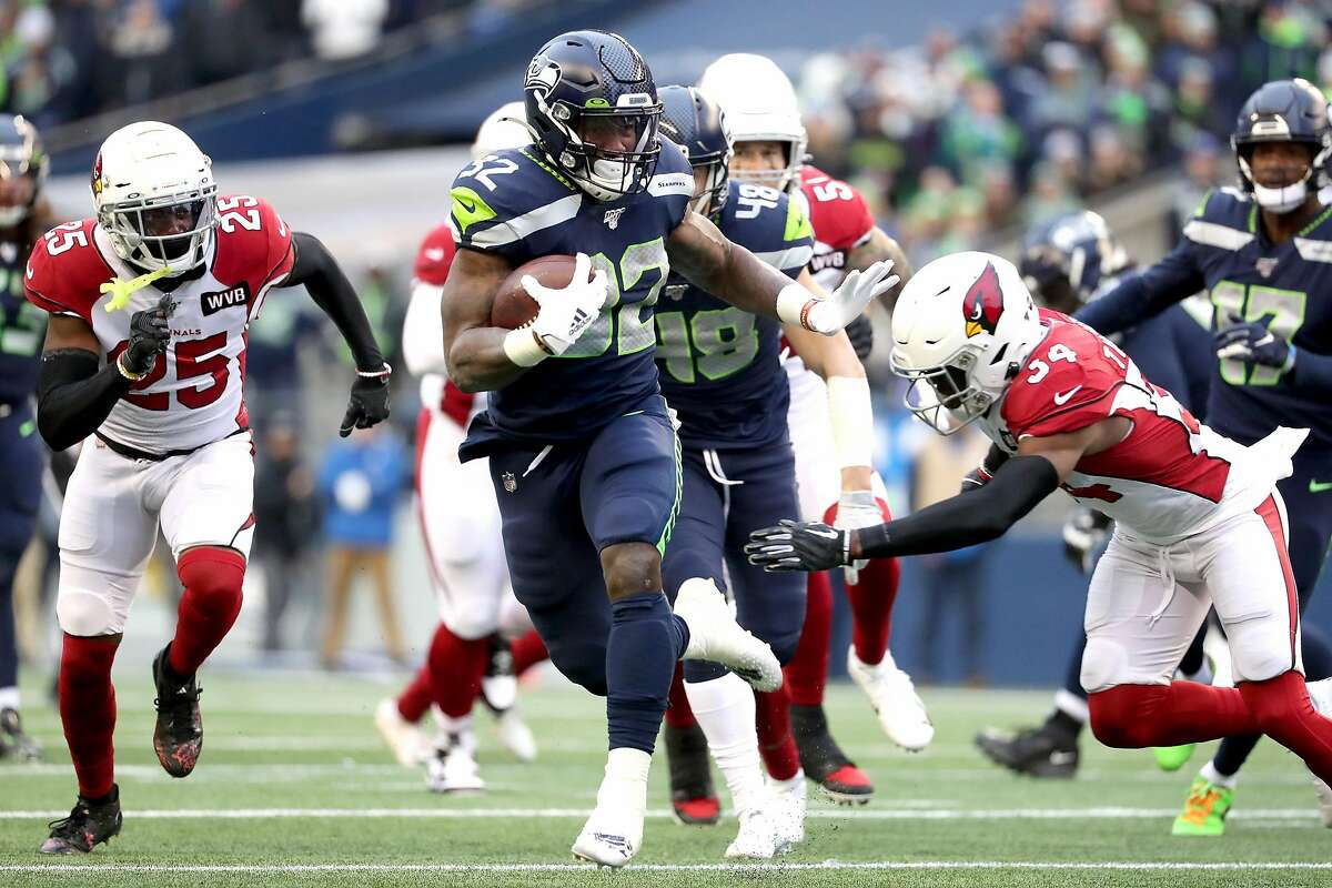 SEATTLE, WASHINGTON - DECEMBER 22: Running back Chris Carson #32 of the Seattle Seahawks carries the ball against the defense of strong safety Jalen Thompson #34 of the Arizona Cardinals during the game at CenturyLink Field on December 22, 2019 in Seattle, Washington. (Photo by Abbie Parr/Getty Images)