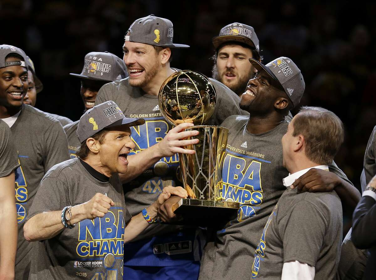 Golden State Warriors forward Draymond Green, with trophy, celebrates with Warriors owners Peter Guber, left, and Joe Lacob after the Warriors won the NBA Finals against the Cleveland Cavaliers in Cleveland, Wednesday, June 17, 2015. The Warriors defeated the Cavaliers 105-97 to win the best-of-seven game series 4-2. (AP Photo/Paul Sancya)(AP Photo/Tony Dejak)