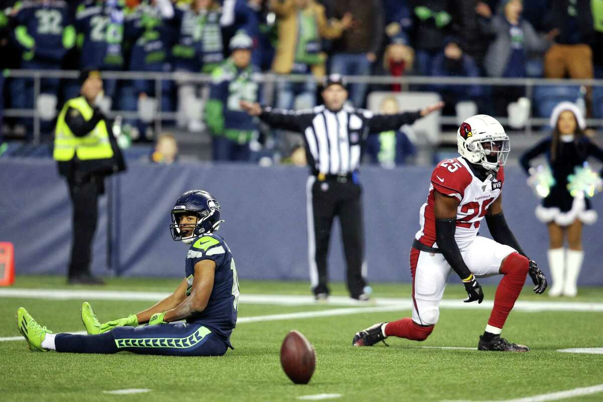 Seattle Seahawks wide receiver Tyler Lockett (16) sits on the ground after a pass to him was broken up by Seattle Seahawks running back Travis Homer (25) and strong safety Budda Baker (32) in the fourth quarter Seattle's game against Arizona, Sunday, Dec. 22, 2019. The Seahawks lost their challenge of the no-pass interference call.