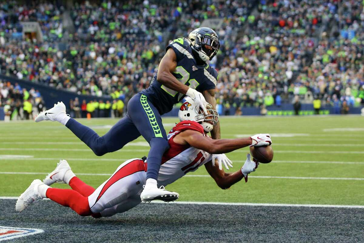 Arizona Cardinals wide receiver Larry Fitzgerald (11) snags a touchdown pass as Seattle Seahawks cornerback Tre Flowers (21) defends at the end of the second quarter during Seattle's game against Arizona, Sunday, Dec. 22, 2019.