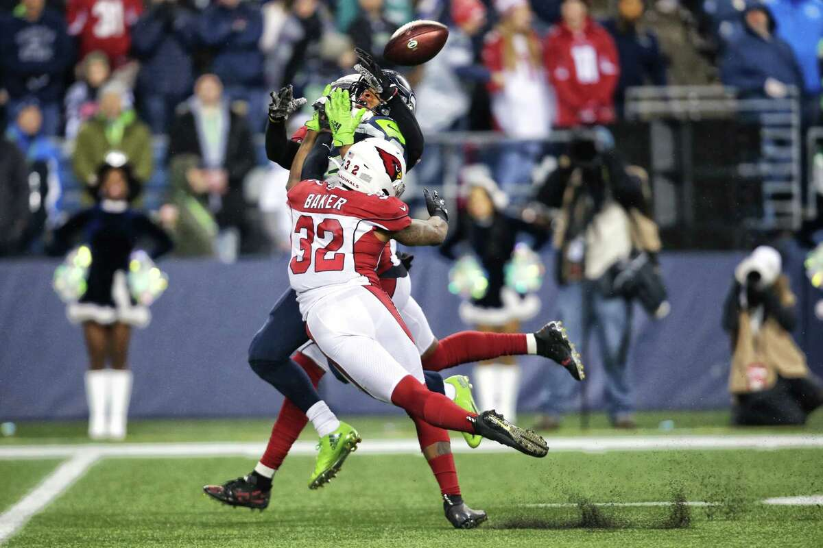 Seattle Seahawks wide receiver Tyler Lockett (16) is clobbered by Arizona Cardinals strong safety Budda Baker (32) and defensive back Chris Jones (25) as he tries to bring in a catch in the fourth quarter Seattle's game against Arizona, Sunday, Dec. 22, 2019. The Seahawks lost their challenge of the no-pass interference call.