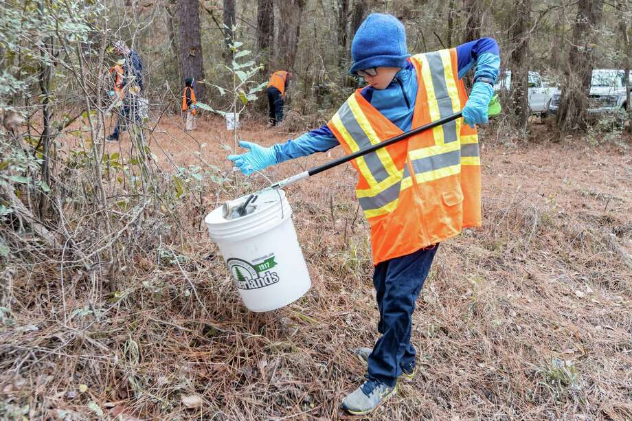 Volunteer Parker Urban, 10,  picks up a can during the park clean-up.The National Park Service held a volunteer clean-up of the Holly Grove Day Use Area in the Menard Creek Corridor Unit of the Big Thicket National Preserve on Saturday morning, December 21, 2019. Fran Ruchalski/The Enterprise Photo: Fran Ruchalski/The Enterprise