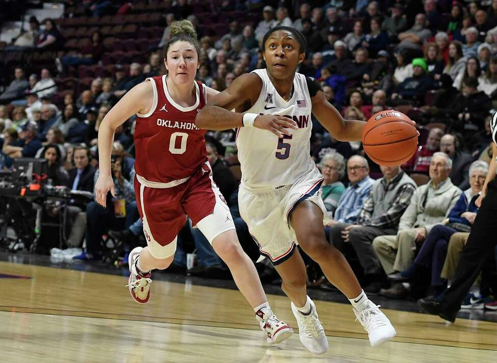 Connecticut's Crystal Dangerfield, right, dribbles to the basket while Oklahoma's Jessi Murcer defends in the second half of an NCAA college basketball game, Sunday, Dec. 22, 2019, in Uncasville, Conn. (AP Photo/Jessica Hill)