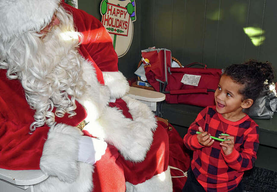 Ericke Hildago, 3, visits Santa Saturday at his house on the downtown square.