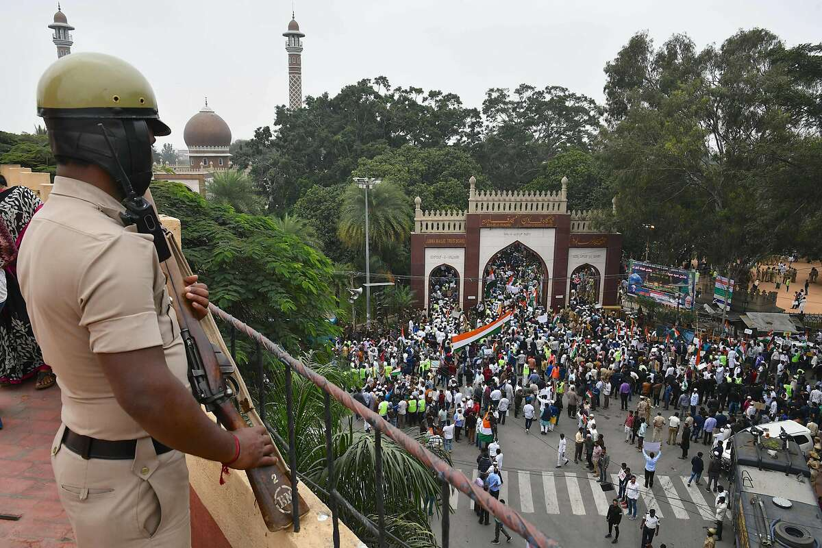 A security personnel stands guard as demonstrators arrive to take part in a rally against India's new citizenship law in Bangalore on December 23, 2019. (Photo by Manjunath Kiran / AFP) (Photo by MANJUNATH KIRAN/AFP via Getty Images)
