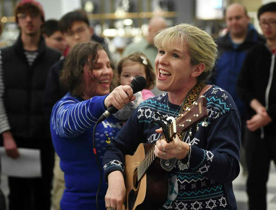 With Rabbi Ita Paskind of Congregation Beth El holding her mic, Rabbi Cantor Shirah Sklar, of Temple Shalom, leads a series of Hannukah songs during a celebration and menorah lighting for the first night of Hannukah at Bloomingdale's at The SoNo Collection in Norwalk, Conn. on Sunday, December 22, 2018. Photo: Brian A. Pounds / Hearst Connecticut Media / Connecticut Post