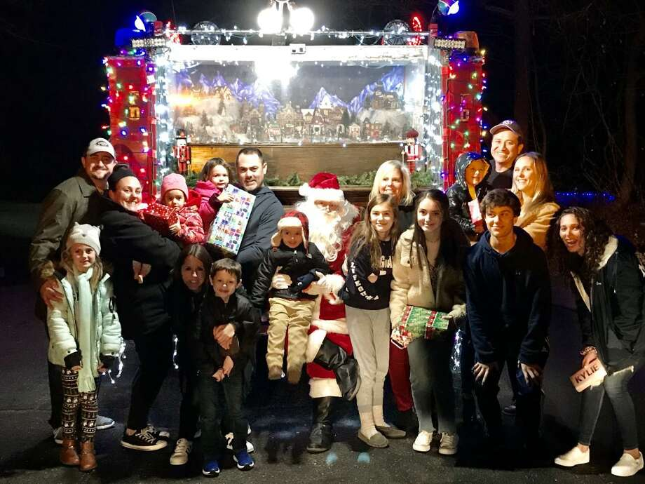 Santa made one of his many stops recently, visiting families on Linley Road. He was brought in on the Long Hill Volunteer Fire Company's lighted firetruck. Photo: Contributed Photo