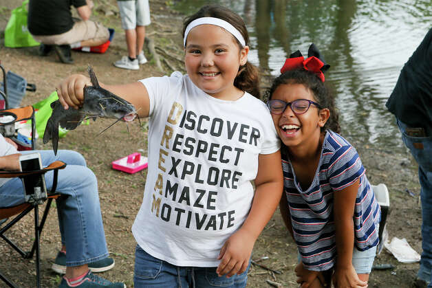 Kalista Medellin, right, laughs as P.J. Shepherd holds a catfish they caught while fishing in Live Oak's annual Junior Fishing Day for children ages 13 and under at Live Oak Park on Saturday, June 1, 2019. Photo: Marvin Pfeiffer / Express-News 2019