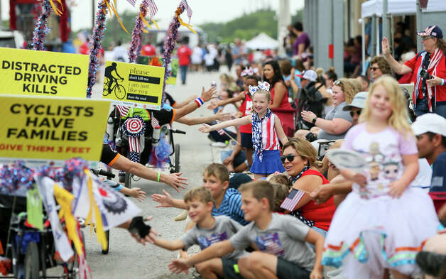Anastasia Palmer, center, 5, high fives riders with the National MS Society with others along Main St. during the Jubilee Parade through downtown Schertz during the city's 44th annual 4th of July Jubilee on Thursday, July 4, 2019. Photo: Marvin Pfeiffer / Express-News 2019