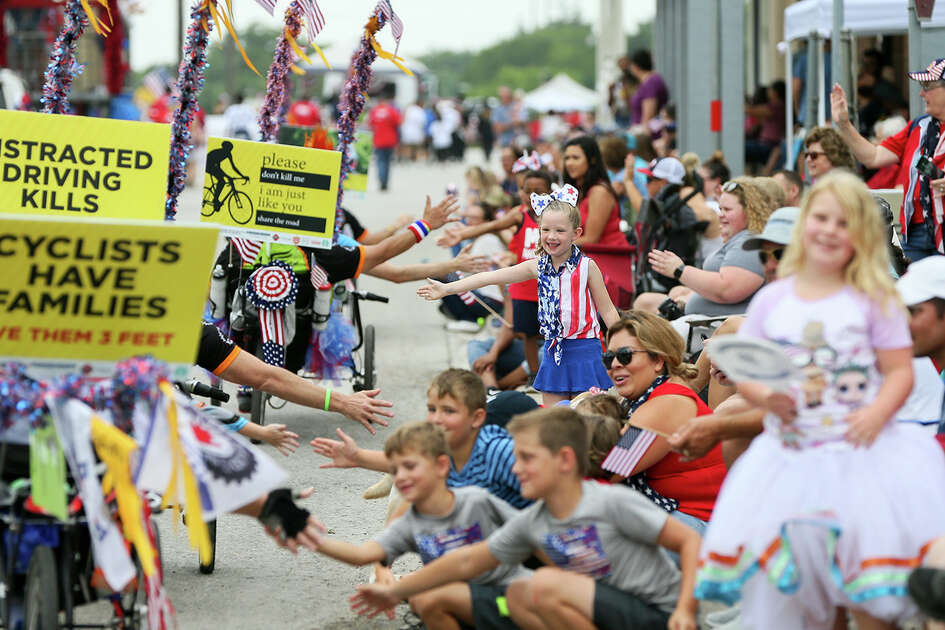 Anastasia Palmer, center, 5, high fives riders with the National MS Society with others along Main St. during the Jubilee Parade through downtown Schertz during the city's 44th annual 4th of July Jubilee on Thursday, July 4, 2019.