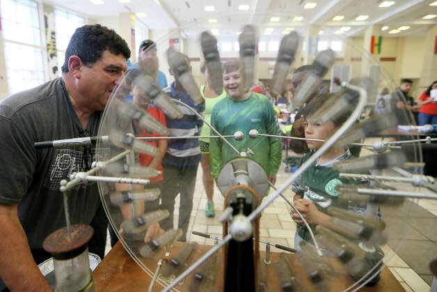 Gil Gomez, left, with St. Mary's University, cranks up a Wimshurst electrostatic generator for a group of students during STEM day at Wagner High School on Saturday, May 18, 2019. Photo: Marvin Pfeiffer / Express-News 2019