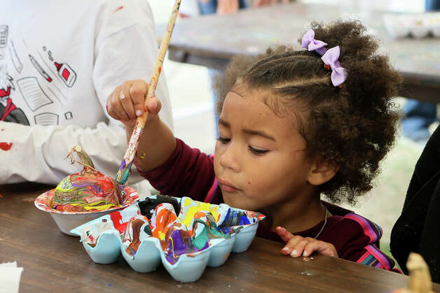 """Aliza Sylvester, 2, paints a pumpkin during Universal City's Fall Fair at the Pumpkin Patch on Saturday, Oct. 12, 2019. The event included a pie throwing """"Cream the Council,"""" a pie eating contest, hayrides, a turkey shoot, petting zoo, pumpkin painting, an inflatable pumpkin jump and craft vendors. Photo: Marvin Pfeiffer / Express-News 2019"""