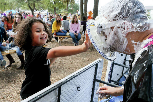 """Atom Galan, 6, throws a whipped cream pie at City Councilman William Shelby during Universal City's Fall Fair at the Pumpkin Patch on Saturday, Oct. 12, 2019. The event included the pie throwing """"Cream the Council,"""" a pie eating contest, hayrides, a turkey shoot, petting zoo, pumpkin painting, an inflatable pumpkin jump and craft vendors. Photo: Marvin Pfeiffer / Express-News 2019"""