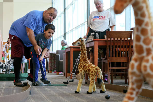 """Cathy Marston, right, watches as Xavier Matos helps his son, Diego Matos, 4, putt past a couple of stuffed giraffes while playing an 18-hole mini golf course winding it's way through book shelves, stacks, and information desks during the Schertz Public Library's fourth annual """"Tee Off for the Library"""" fundraiser event on Saturday, June 22, 2019. Participants were able to escape the summer heat and relax indoors with a round of mini golf, a hot dog, chips and a drink, all for $5 per person. Photo: Marvin Pfeiffer / Express-News 2019"""