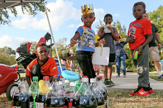Messiah Williamson, 4, second from left, tries his hand at the 2-liter ring toss at the 2019 National Night Out hosted by West End Hope In Action organization at the West End Park on Tuesday, Oct. 1, 2019. The family friendly event featured student song and dance performances, a bicycle parade, a senior citizen fashion show and free food and drinks. Photo: Marvin Pfeiffer / Express-News 2019