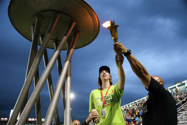 Morgan Hartman lights the cauldron with the help of SAPD officer Thomas Alonzo during the Opening Ceremonies for the 2019 Summer Games of Special Olympics Texas (SOTX) at Toyota Field on Friday, May 3, 2019. Photo: Marvin Pfeiffer / Express-News 2019