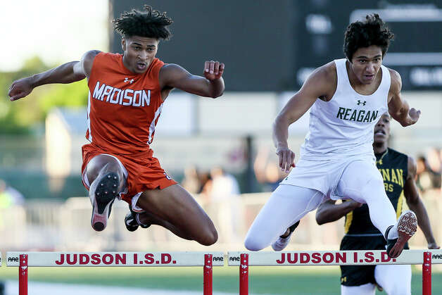 Madison's Dante Heaggans, left, and Reagan's Noah Crawford clear the final hurdle in the boys 300-meter hurdles during the District 27/28 6A area track and field meet at Rutledge Stadium on Thursday, April 18, 2019. Heaggans beat Crawford by .02 seconds, winning the event with a time of 39.06 seconds. Photo: Marvin Pfeiffer / Express-News 2019