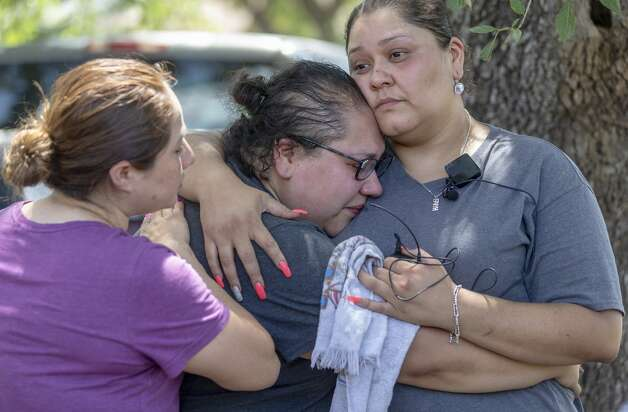 Sisters Erica Solis, center, and Christina Gonzalez, right, embrace Tuesday, Aug. 6, 2019, outside the home in the 7500 block of Dream Valley where an apparent triple homicide-suicide Monday evening left four of their family members dead. Photo: William Luther/Staff Photographer