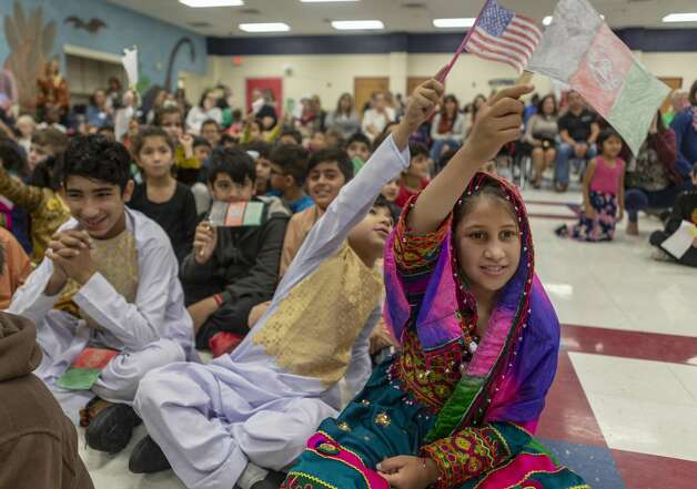 Hassina Safi, of Afghanistan, waves her home country's flag Thursday, Oct. 24, 2019, during her elementary school's Parade of Nations. Colonies North Elementary School, the home school to many of the refugees who are placed by Catholic Charities in the Northside ISD, serves students from numerous countries. Photo: William Luther/Staff
