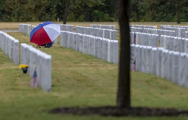 A person visiting a gravesite Thur., Nov. 7, 2019, at Ft. Sam Houston National Cemetery uses an umbrella to stay dry as a cold front brings widespread light rain and north winds to the area. After returning to a south flow during the weekend, the Austin/San Antonio National Weather Service office predicts Veterans Day on Monday will see winds shift to the north with gusts as high as 30 mph, a 40 percent chance of rain and a low Monday night in the 30s. Photo: William Luther/Staff