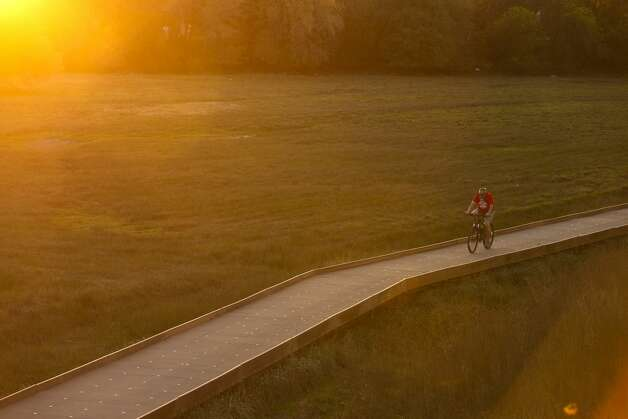A bicyclist makes his way close to sunset Wednesday, Dec. 4, 2019, along the Salado Creek section of the Howard W. Peak Greenway Trail System. The system includes about 69 miles of trails that form a loose circle around the city. Photo: William Luther/Staff