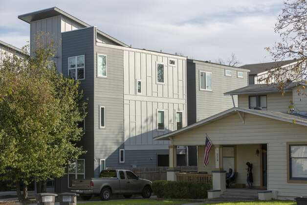 The residents of 934 W. Craig Place sit on their porch Thursday, Dec. 5, 2019, as a the three story, multifamily infill development rises behind them. Photo: William Luther/Staff
