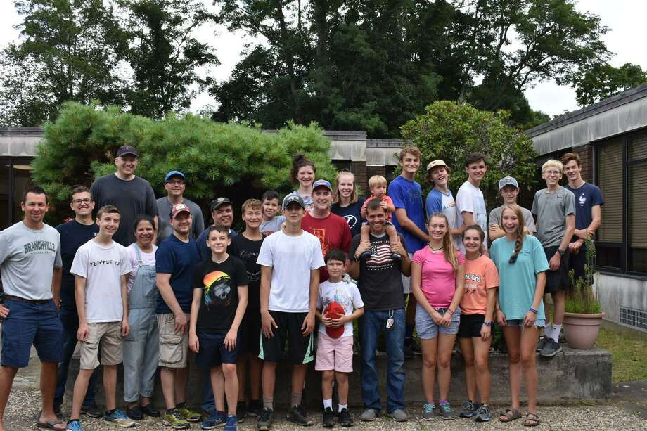 Ridgefield High School junior Luke Nelson, center in hat, helped clean up the courtyard at Branchville Elementary School this fall. Pictured around Nelson is his clean-up crew, including Principal Keith Margolus on the far left. Photo: Contributed Photo