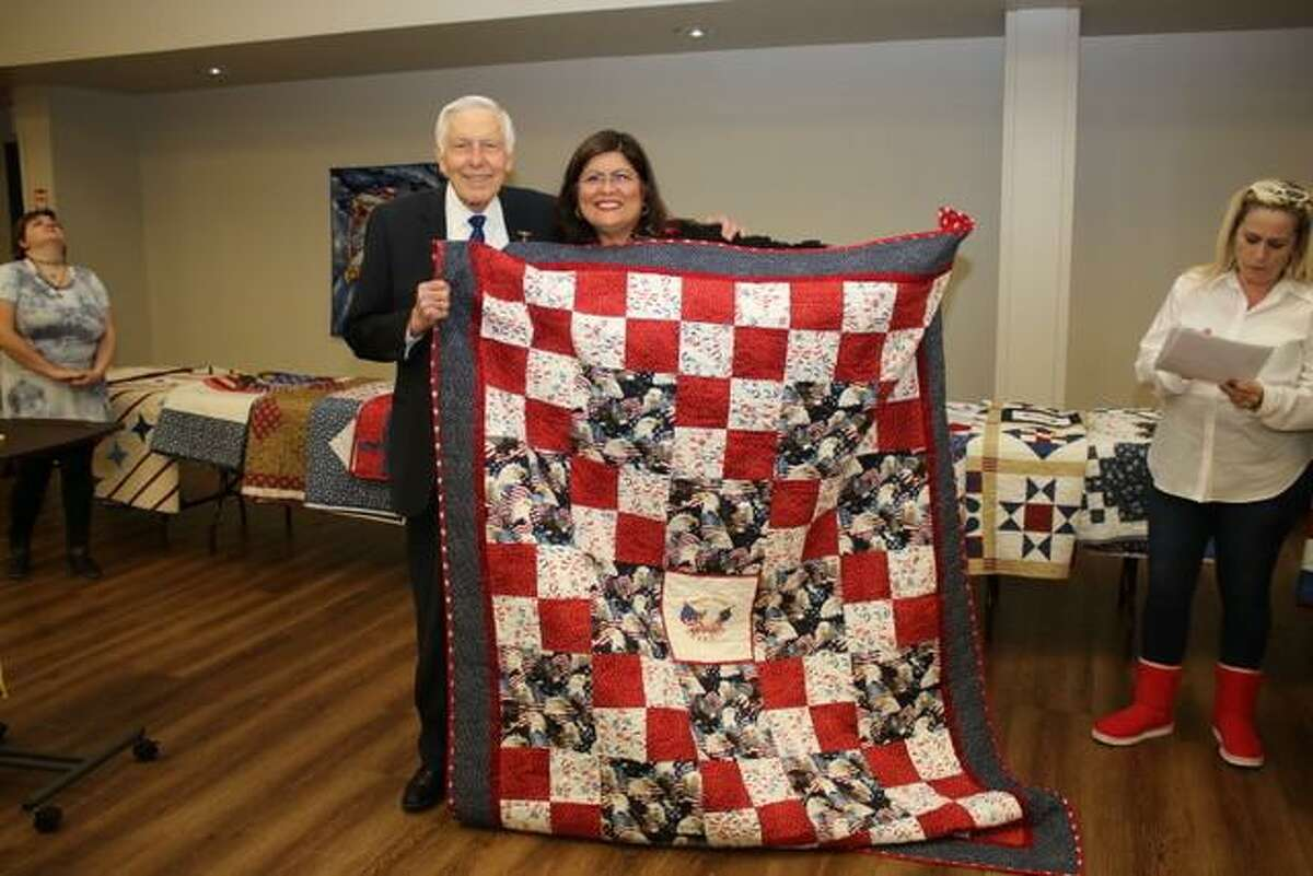 Paul Edward Marting, (LCDR), United States Navy Lt Commander, Fighter Pilot Korean War was presented a quilt made by Mary Olivarez of the Golden Needles Quilt Guild.