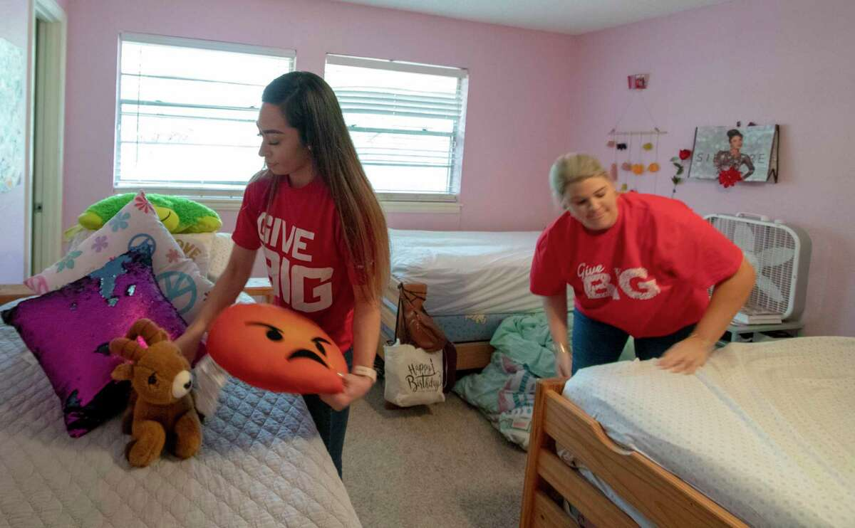Rosaura Martinez, left, and Kelsey Wells with Mattress Firm put sheets and toys back onto beds after replacing the mattresses Tuesday, March 12, 2019 at the Treehouse Center in Conroe. Mattress Firm donated 25 mattresses to the center.