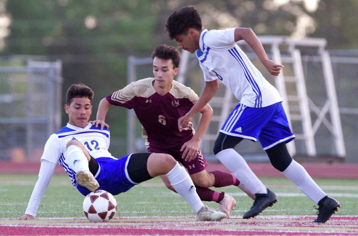Angel Hernandez #12 of New Caney tries to makes a pass to Ricardo Ramirez in front of Alexis Oliveras #4 of Magnolia West during the first period of a Region III-5A bi-district soccer match at Magnolia West High School, Friday, March 29, 2019, in Magnolia.