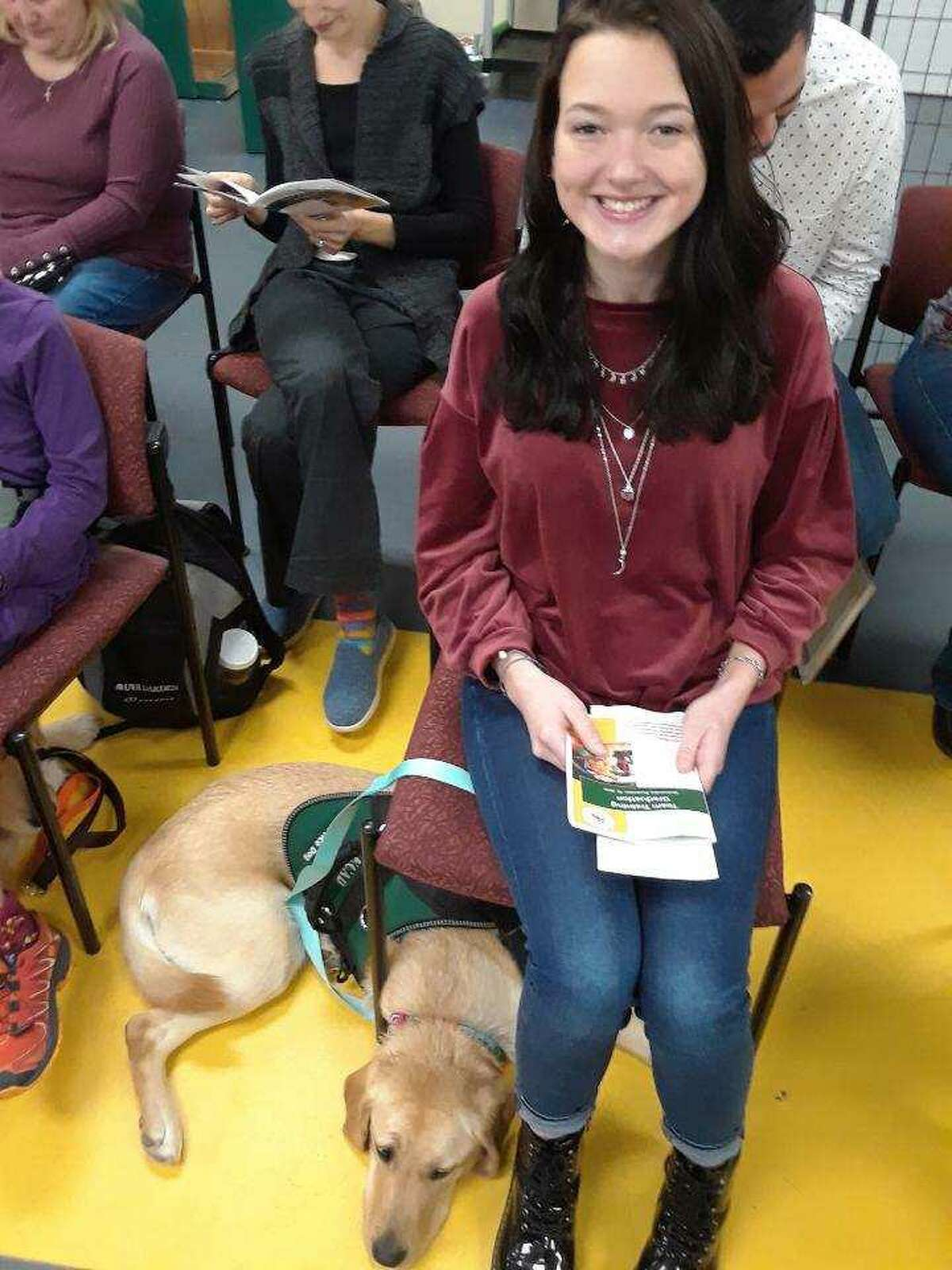 Grace Cutshall of North Carolina sits with her service dog Royale at ECAD, a non-profit organization in Winchester.