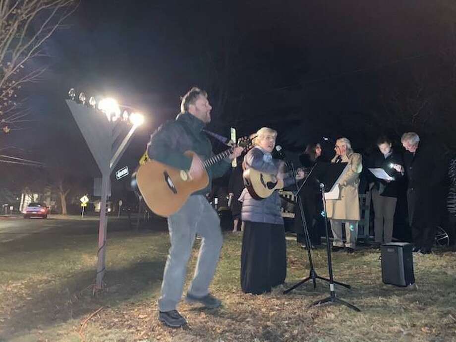The first night of Chanukah was celebrated at God's Acre in New Canaan on Sunday, Dec. 22, 2019. Assistant Rabbi of Temple Shalom of Norwalk played guitar and sang with Cantor Shirah Sklar, also from Temple Shalom. Photo: Grace Duffield / Hearst Connecticut Media