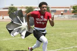 Jordan Battles drags the open parachute as he works out with the coaching of his dad, Shaun Battles, at Brandeis High School on July, 31 2019.