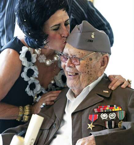 Rosalinda Cardenas kisses Odon Cardenas who was celebrating his 100th birthday with family and friends at the Plaza Club in San Antonio on Aug. 3, 2019. Photo: Tom Reel/Staff Photographer