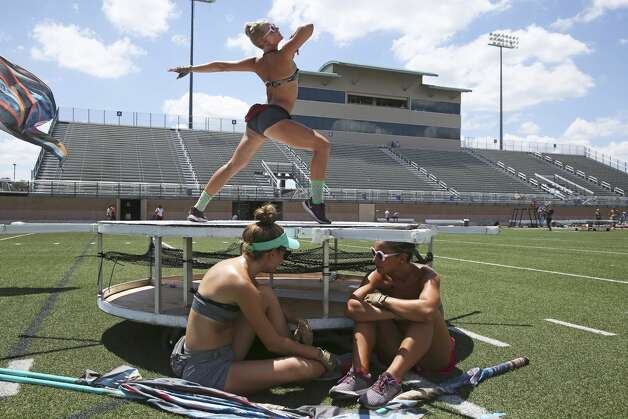 Color guard members Amy Edwards, left, and Becca Lamanna take advantage of the sparse shade available under a platform on the field. Fellow performer Markus Blankenship goes through her routine above as the Crossmen of San Antonio practice at Farris Stadium July 19, 2019 in preparation for Saturday's Drum Corps International Southwestern Championship at the Alamodome. Photo: Tom Reel/Staff Photographer