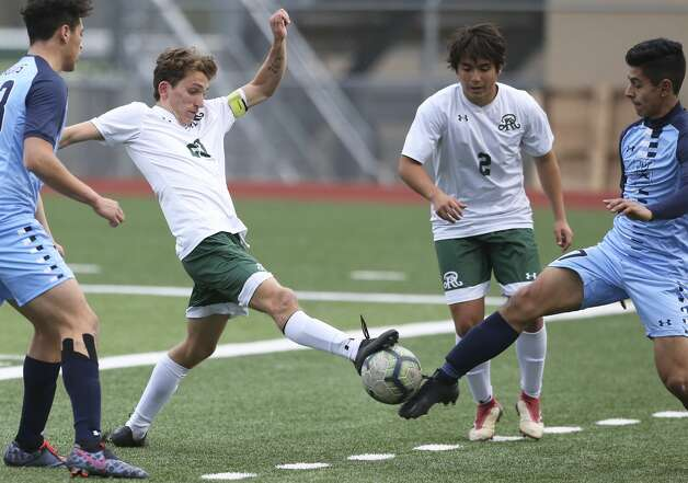 Reagan's Michael Morell stretches in to challenge Johnson's Santiago Bustos as Johnson plays Reagan in boys soccer at Comalander Stadium on Jan. 29, 2019. Photo: Tom Reel/Staff Photographer