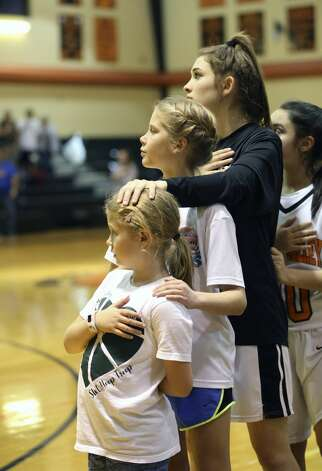Medina Valley Junior Kamryn Griggs embraces sisters Juliana Russell, left, and Jordyn Russell during the national anthem on February 5, 2019. The sisters are the daughters of Medina Valley girls basketball coach Justin Russell and Katie Russell. Katie Russell died after a cardiac arrest on Jan. 7, 2019. Photo: Tom Reel/Staff Photographer