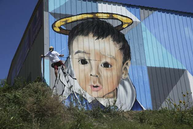 Artist Colton Valentine nears the completion of a mural on July 27, 2019, in honor of King Jay Davila, the 8-month old infant whose body was found buried in a field in January. The artwork was completed despite high temperatures and sunlight on the metal wall of a building in the 1300 block of Jerry, off of Hildebrand and Interstate 10. Photo: Tom Reel/Staff Photographer