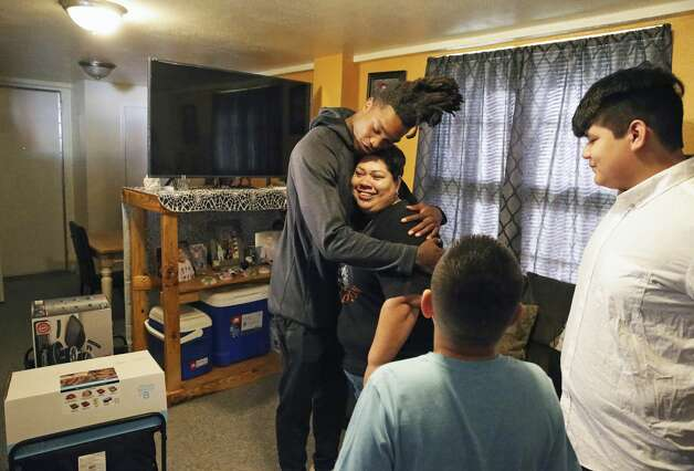 Terry Ann Colunga gets a hug from Spurs guard Lonnie Walker IV as he delivers Thanksgiving gifts on the Westside on Nov. 26, 2019. Photo: Tom Reel/Staff Photographer