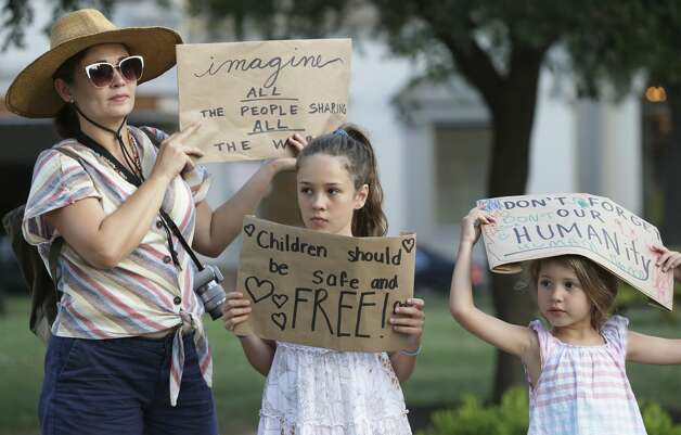 Caroline Atwood, left, and her daughters Catherine, center, and Elisabeth hold up signs they fashioned on plain paper for the Lights for Liberty event at Travis Park on July 12, 2019. Photo: Tom Reel/Staff Photographer