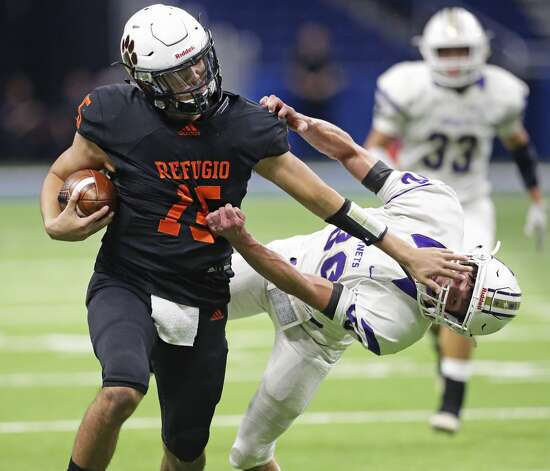 Bobcat quarterback Austin Ochoa drops Hornet tackler Brady Shelton with a stiff arm on a long run in the first half as Refugio plays Holland in state quarterfinal football action at the Alamodome on Dec. 5, 2019. Photo: Tom Reel/Staff Photographer