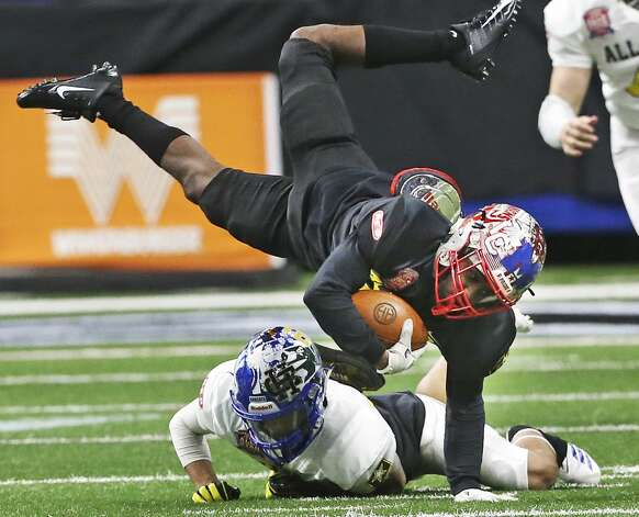 Kenyon Morgan flies over a trip up tackle on a return for Team Black during the San Antonio Sports All-Star Game at the Alamodome on Jan. 5, 2019. Photo: Tom Reel/Staff Photographer