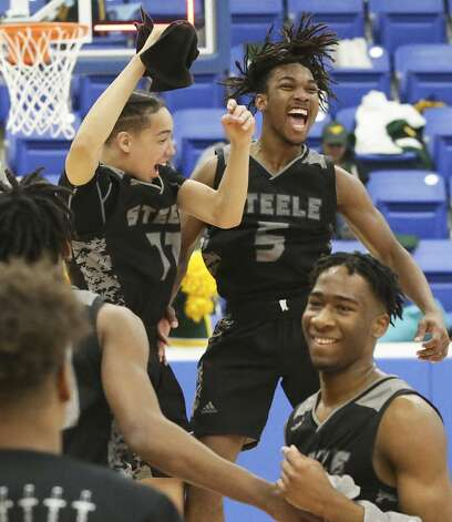 Nick Moore, left, and Quincey Sheperd jump in celebration as Steele defeats Laredo Nixon in the Region IV-6A boys basketball finals at Northside Sports Gym on March 2, 2019. Photo: Tom Reel/Staff Photographer