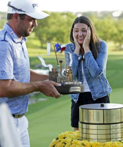 Mallory Conners watches Corey Conners pick up the trophy as the winner of the Valero Texas Open after the final round at the AT&T Oaks Course at TPC San Antonio on April 7, 2019. Photo: Tom Reel/Staff Photographer