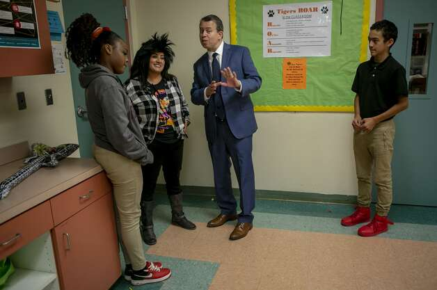 Flanked by student guides Alasia Brown, 13, far left, and Omar Lopes, 13, far right, Poe Middle School Principal Christine Perez and SAISD Superintendent Pedro Martinez talk as Martinez visits Poe Middle School in San Antonio on Oct. 29, 2019. Photo: Josie Norris/The San Antonio Express-News