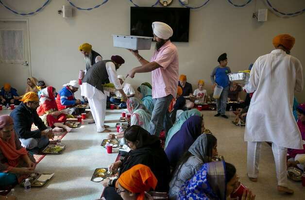 Volunteers serve the langar, the traditional community meal for all visitors after services, at the Sikh Dharamsal of San Antonio during a community open house as part of the commemoration of the 550th birth anniversary of Guru Nanak, the first Guru of the Sikhs and founder of Sikhism, on Dec. 8, 2019. Langar also represents the rejection of a caste system and some of the core tenants of Sikhism such as equality, sharing of resources and service. Photo: Josie Norris/Staff Photographer